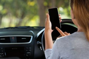 woman using phone in car on road